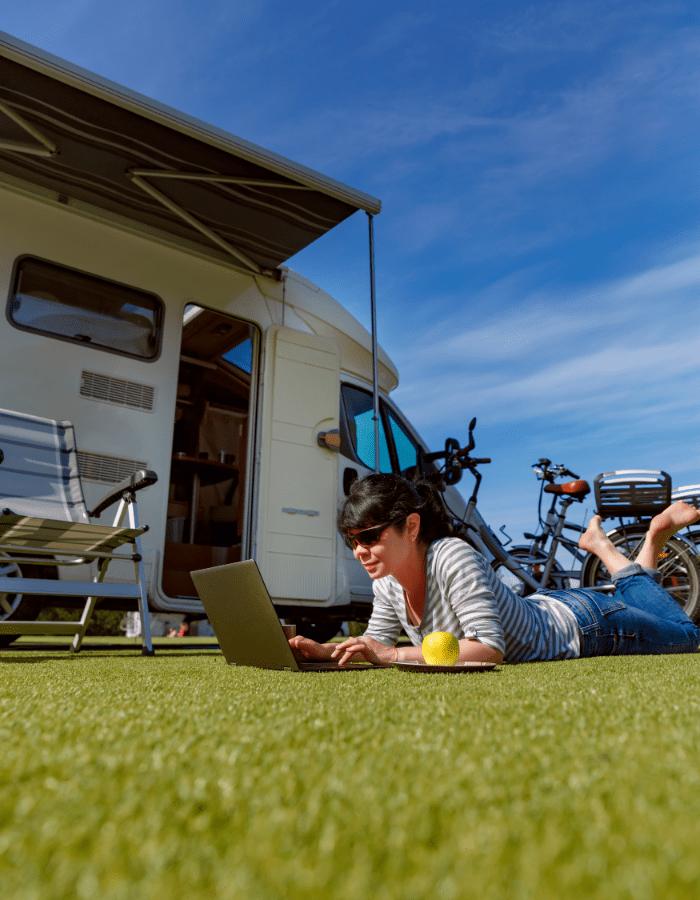 Devant sa roulotte, une femme profite de son portable avec connexion Internet ikonek sur son terrain de camping.